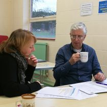 Clare and David are seated a a table looking at research papers. David is drinking a cup of coffee.