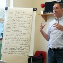 Andrew stands next to flip chart talking to group.