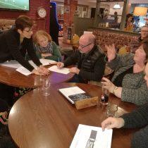 Five people seated around pub table talking.