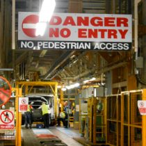 Warning sign above narrow section of production line reads 'Danger No Entry - no pedestrian access' 2013.