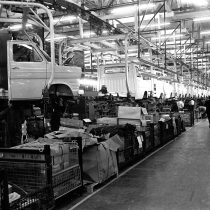 A line of Ford Transits suspended on the monorail production line 1973, men working underneath.