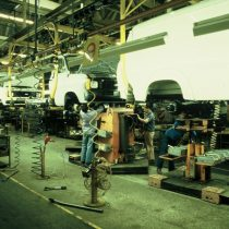 Men working underneath the moving production line of Transits, suspended on the monorail 2005.