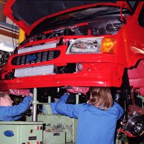 Two workers fitting an engine underneath the front end of a suspended Transit van on the 'Merry Go Round' 1996.