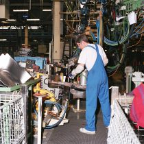 A worker lifting heavy machinery in the Body Shop 2001.