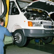 A worker using a machine to tighten the wheel nuts on a Transit van in the Trim Shop 1996.